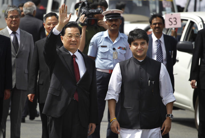Chinese President Hu Jintao, left, waves as Indian minister of state for Information Technology, Jyotiraditya Scindia, right, receives him at the airport in New Delhi, India, Wednesday, March 28, 2012. Hu visited New Delhi to attend BRICS summit. (AP Photo/Saurabh Das)