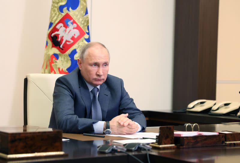Russian President Vladimir Putin chairs a a video conference meeting outside Moscow