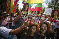 Myanmar nationals living in Thailand hold pictures of deposed Myanmar leader Aung San Suu Kyi as they protest against the military coup in front of the United Nations building in Bangkok, Thailand, Sunday, March 7, 2021. (AP Photo/Nava Sangthong)