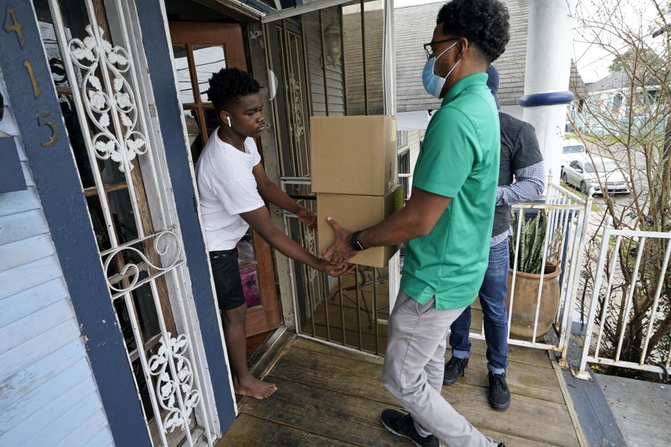 "David Russ, left, receives boxes of meals for his grandparents from Courtney Jones of Revolution Foods in New Orleans on Thursday, Feb. 11, 2021. ""We've had quite a few people tell us that they would not have meals, they literally would not have food if not for the program,"" said Darnell Head, of Revolution Foods, which operates the program in New Orleans. (AP Photo/Gerald Herbert)"