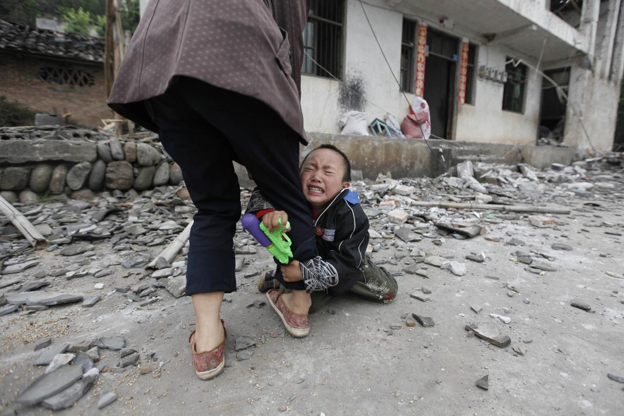 RNPS - PICTURES OF THE YEAR 2013 - A boy holds his mother's leg as he cries in front of their damaged house after a strong 6.6 magnitude earthquake at Longmen village, Lushan county in Ya'an, Sichuan province April 21, 2013. Rescuers poured into a remote corner of southwestern China on Sunday as the death toll from the country's worst earthquake in three years climbed to 164 with more than 6,700 injured, state media said. REUTERS/Jason Lee (CHINA - Tags: DISASTER ENVIRONMENT TPX)