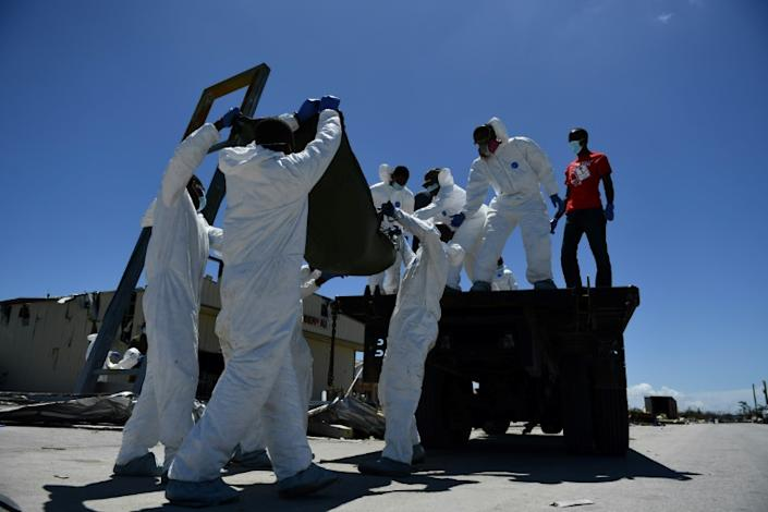 Hands and face protected by latex gloves and masks, the recovery team hoists bodies onto an old flatbed truck alongside other victims (AFP Photo/Brendan Smialowski)