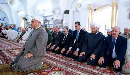 Syria's President Bashar al-Assad (3rd R) attends prayers on the first day of the Muslim holiday of Eid al-Fitr, inside a mosque in Hama, in this handout picture provided by SANA on June 25, 2017, Syria. SANA/Handout via REUTERS