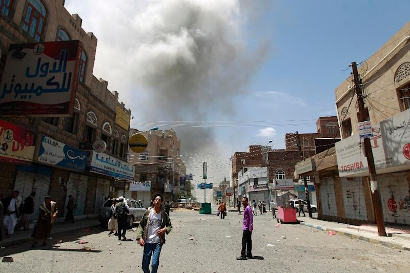 Yemeni men stand on a street as smoke billows following reported air strikes in Sanaa, on May 10, 2015 (AFP Photo/Mohammed Huwais)