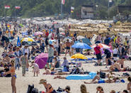 People spend the day at the beach of the Baltic Sea in Scharbeutz, northern Germany, on a sunny Saturday, June 5, 2021. It was the first run to the beaches after some Corona restrictions in that region ended. (AP Photo/Michael Probst)