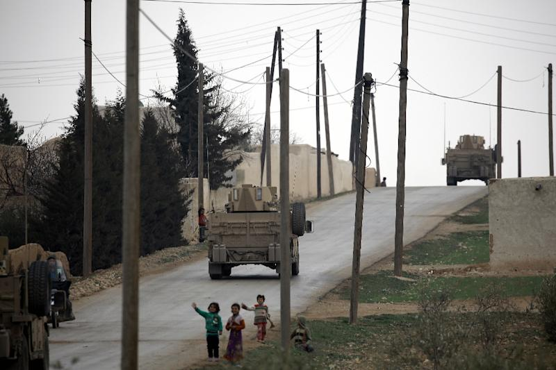 Children wave to US forces patrolling the roads surrounding the northern Syrian city of Manbij on March 3, 2017