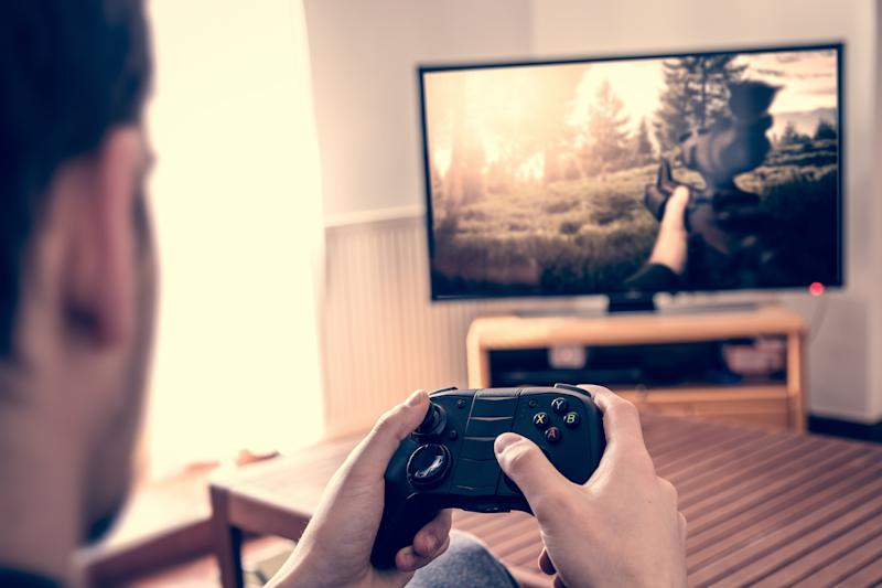 A man plays video games using a handheld console and a television screen.