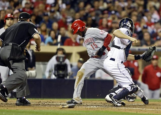 Cincinnati Reds' Derrick Robinson beats the throw and the tag by San Diego Padres catcher Nick Hundley while scoring from third on an infield ground ball in the fifth inning of a baseball game in San Diego, Monday, July 29, 2013. The umpire is Brian Knight. (AP Photo/Lenny Ignelzi)