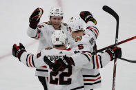 Chicago Blackhawks center Ryan Carpenter (22) celebrates his goal against the Boston Bruins with teammates center Zack Smith (15) and defenseman Connor Murphy (5) in the first period of an NHL hockey game, Thursday, Dec. 5, 2019, in Boston. (AP Photo/Elise Amendola)