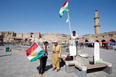 An Iraqi Kurdish man holds a Kurdish flag in Erbil