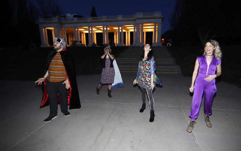 In this Wednesday, April 8, 2020, photograph, Brice Maiurro, Shelsea Ochoa, Anna Beazer and Kali Healf, from left, howl in Cheesman Park in Denver, during. the coronavirus outbreak. From California to New York, some Americans are taking a moment each night at 8 o'clock to howl as a way of thanking the health care workers and first responders who are fighting the coronavirus pandemic.  (AP Photo/David Zalubowski)