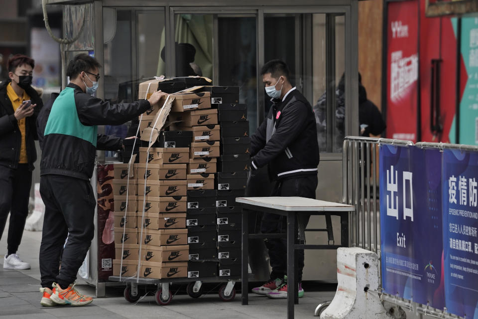 Workers wearing face masks to help curb the spread of the coronavirus push a cart loaded with shoes made by Nike past a security post at a shopping mall in Beijing, Thursday, Jan. 14, 2021. China's exports rose in 2020 despite pressure from the coronavirus pandemic and a tariff war with Washington, boosting its politically volatile trade surplus to $535 billion, one of the highest ever reported. (AP Photo/Andy Wong)
