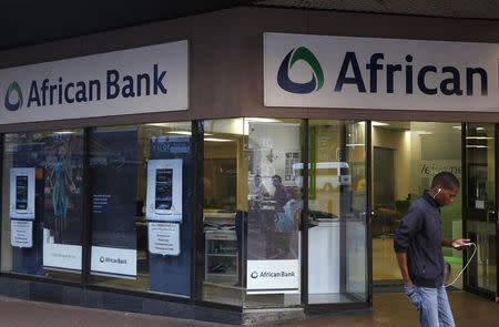 A man walks past a branch of African Bank in Cape Town