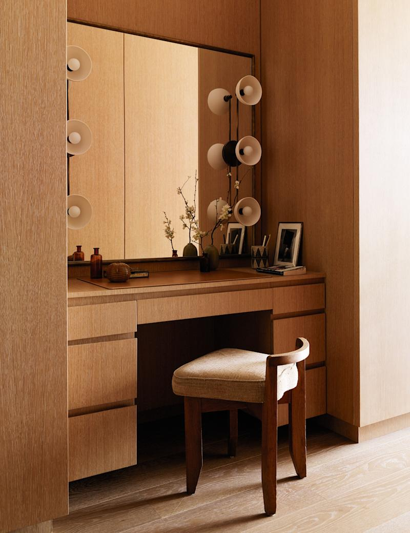 Santos designed the perfect minimalist vanity from custom antique brass and cerused oak with sconces by Apparatus and a small chair by Guillerme et Chambron, purchased from Morentz.
