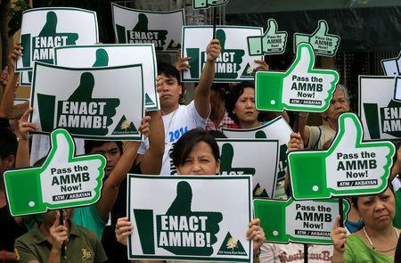 """Pro-environment activists gather as they carry placards calling for the passing of the """"Alternative Minerals Management Bill"""" mining law during a rally in front of the Senate building in Pasay city, metro Manila, Philippines August 25, 2016. REUTERS/Romeo Ranoco"""