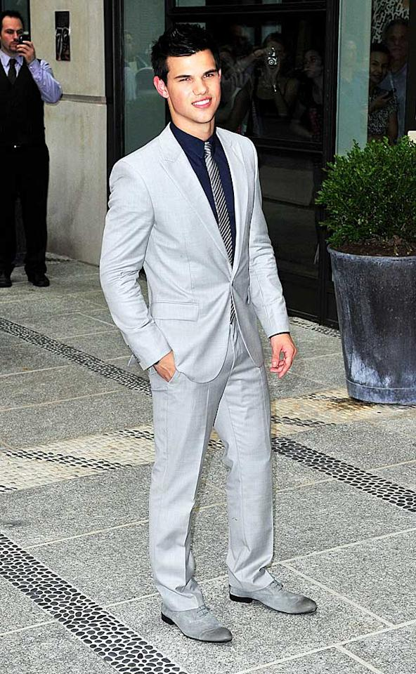 "Opting for his classic ""side-lean"" pose, Kristen's gorgeous co-star, Taylor Lautner, had the girls swooning in his beautifully cut gray suit, navy shirt, and classic striped tie. Ahmad Elatab/<a href=""http://www.splashnewsonline.com"" target=""new"">Splash News</a> - June 28, 2010"