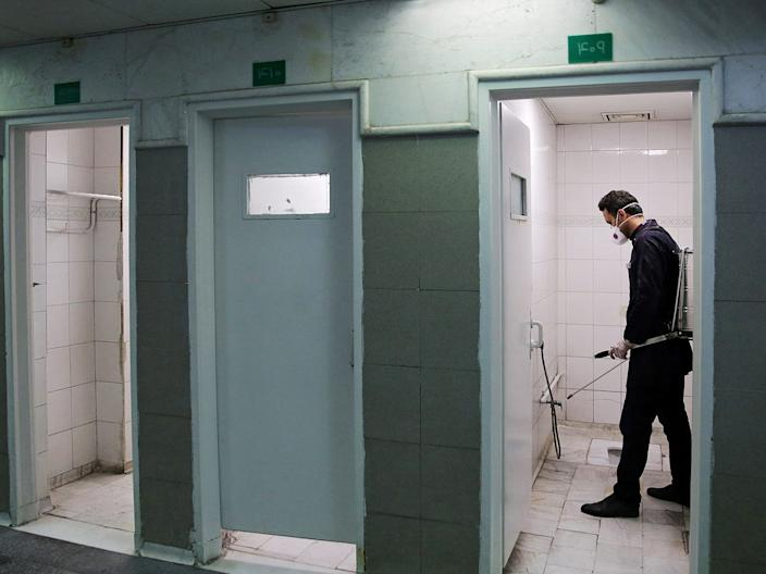 <br>A member of the medical team sprays disinfectant to sanitize bathrooms in a shrine in Iran on February 27.
