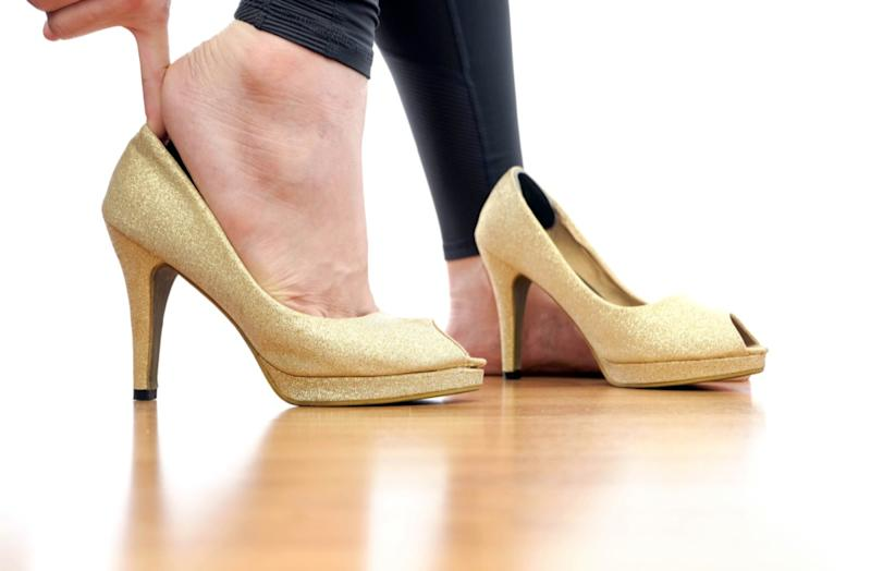 Women are wearing gold high heels. Her hand catches high heels.
