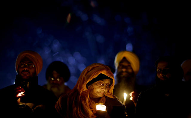 <p>Surjit Kaur Gill, of Worcester, Mass., joins a group of Sikhs from around the Northeastern U.S., in a moment of prayer as a memorial service is broadcast over a loudspeaker outside Newtown High School for the victims of the Sandy Hook Elementary School shooting, Dec. 16, 2012, in Newtown, Conn. (AP Photo/David Goldman) </p>