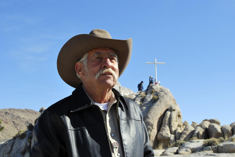 This photo provided by Liberty Institute shows Henry Sandoz standing below a new, 7-foot steel cross on the same hilltop before more than 100 people. People gather beneath a 7-foot-tall World War I memorial cross on a rocky hilltop within a national park at its rededication in the Mojave Desert community of Cima, Calif., Sunday, Nov. 11, 2012. Sandoz had cared for the original 1930s cross as part of a promise to a dying World War I veteran. The original earlier cross had stood at the site for decades before being deemed unconstitutional and removed because it stood on public land. The site is now in private hands as part of a land swap with the National Park Service that ended the longstanding legal dispute, which had become entangled in the thorny issues of patriotism and religion. (AP Photo/Liberty Institute)