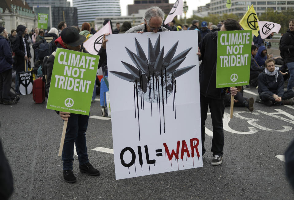 Climate protestors block a road leading to Britain's Parliament in central London Monday, Oct. 7, 2019, in an attempt to disrupt the heart of government. (AP Photo/Matt Dunham)