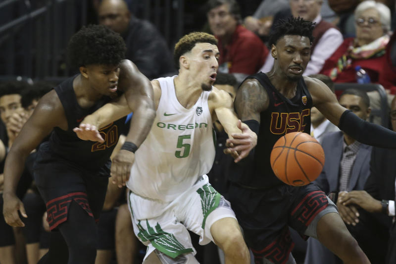 Southern California's Ethan Anderson, left, and Jonah Mathews, right, battle Oregon's Chris Duarte, center, for the ball during the second half of an NCAA basketball game in Eugene, Ore., Thursday, Jan. 23, 2020. (AP Photo/Chris Pietsch)