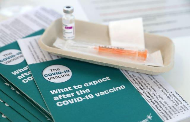 Covid-19 vaccine leaflets sit beside a vaccine vial (Andrew Milligan/PA)