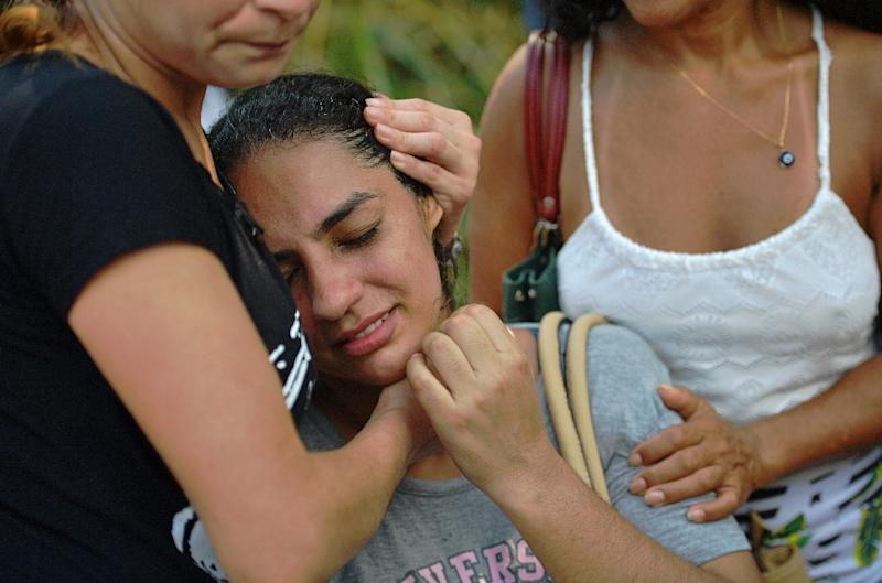 A woman is comforted after two buildings collapsed in the Muzema favela of Rio de Janeiro, Brazil, on April 12, 2019