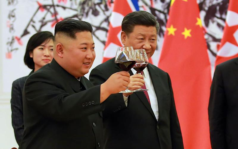 North Korean leader Kim Jong Un (L) and Chinese President Xi Jinping (R) making a toast at the Great Hall of the People in Beijing - AFP