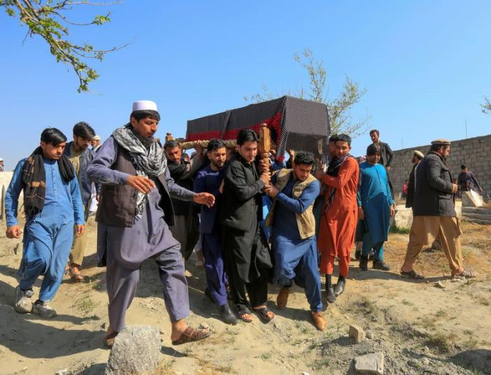 FILE PHOTO: Afghan men carry the coffin of one of three female media workers who were shot and killed by unknown gunmen, in Jalalabad