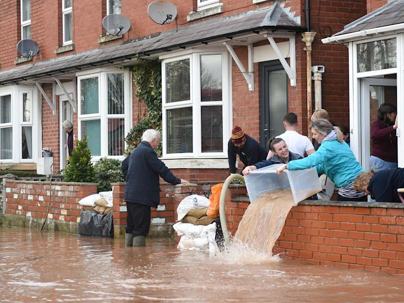 People bail water out of flooded homes after the River Wye burst its banks in Ross-on-Wye, western England: AFP