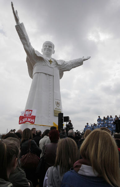 Residents attend the unveiling ceremony of the statue of the late Pope John Paul II in Czestochowa, Poland, on Saturday, April 13, 2013. Archbishop Waclaw Depo unveiled the 13.8-meter (45.3-foot) white fiberglass figure that was funded by a businessman, Leszek Lyson, in gratitude for what he believes was an intervention by the late pontiff in saving his drowning son. At front is a small replica statue. (AP Photo/Czarek Sokolowski)