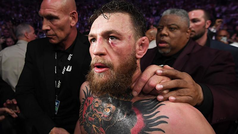 Conor McGregor with a swollen face and being escorted out after a loss.