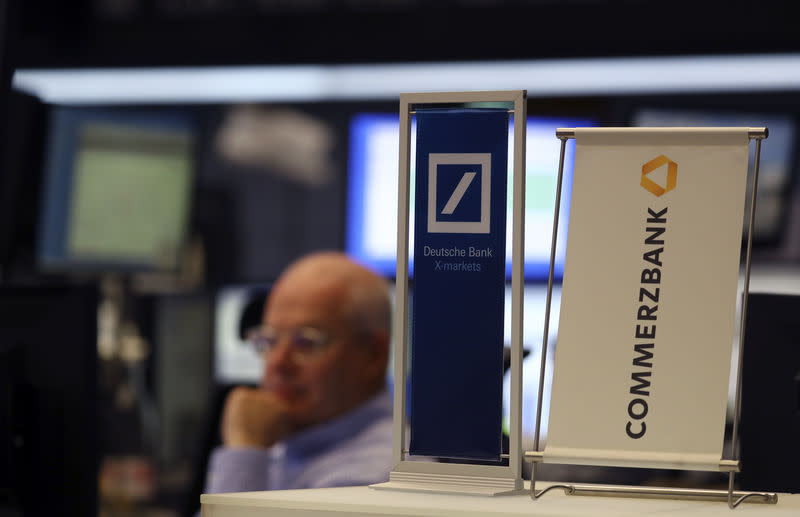 Banners of Deutsche Bank and Commerzbank are pictured in front of a trader at the stock exchange in Frankfurt