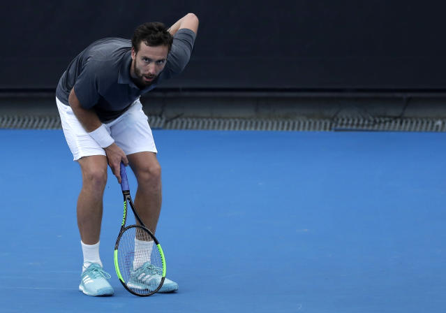 Latvia's Ernests Gulbis holds his back during his first round match against Switzerland's Stan Wawrinka at the Australian Open tennis championships in Melbourne, Australia, Tuesday, Jan. 15, 2019. (AP Photo/Kin Cheung)