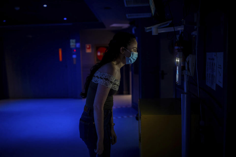 "A cast member of the opera ""Rusalka"" gets a temperature check as part of the COVID-19 protocol measures prior to a performance at the Teatro Real in Madrid, Spain, on Friday, Nov. 13, 2020. The theater is one of the few major opera houses that have reopened during the pandemic, although to smaller audiences. (AP Photo/Bernat Armangue)"