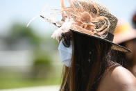 A woman wears a face mask to protect from the spread of COVID-19 ahead of the Preakness Stakes horse race at Pimlico Race Course, Saturday, May 15, 2021, in Baltimore. (AP Photo/Nick Wass)