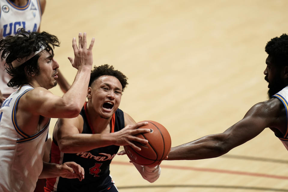 Pepperdine guard Colbey Ross drives to the basket as UCLA guard Jaime Jaquez Jr., left, and forward Cody Riley, right, defend during the second half of an NCAA college basketball game Friday, Nov. 27, 2020, in San Diego. (AP Photo/Gregory Bull)