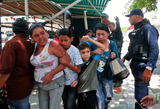 <p>Police officers disperse the relatives of prisoners who were waiting to hear news about their family members imprisoned at a police station when a riot broke out, in Valencia, Venezuela, Wednesday, March 28, 2018. In a state police station housing more than one hundred prisoners, a riot culminated in a fire, requiring authorities to open a hole in a wall to rescue the inmates. (AP Photo/Juan Carlos Hernandez) </p>