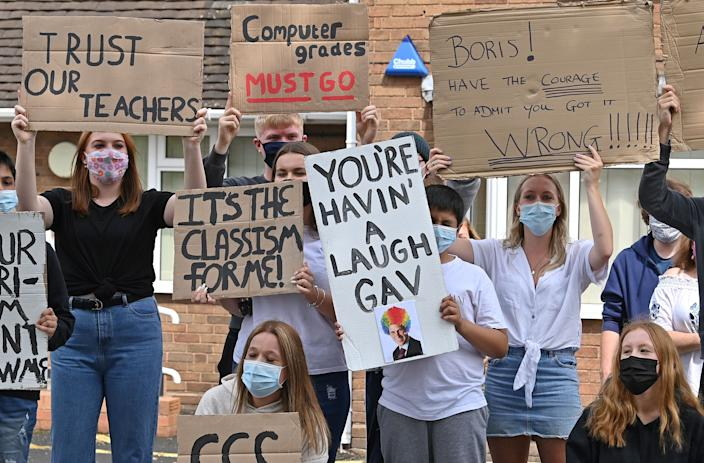 """Students hold placards as they take part in a protest march from Codsall Community High School to the constituency office of Gavin Williamson, Conservative MP for South Staffordshire and Britain's current Education Secretary, in Codsall near Wolverhampton, central England on August 17, 2020, to demonstrate against the downgrading of A-level results. - Britain's government announced a u-turn Monday, meaning that A-level students in England will be see their grades increased. Williamson apologised to students and parents affected by """"significant inconsistencies"""" with the grading process introduced after exams were cancelled due to COVID-19. (Photo by Paul ELLIS / AFP) (Photo by PAUL ELLIS/AFP via Getty Images)"""