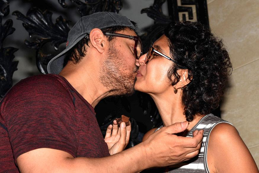 Aamir Khan and his wife Kiran Rao Khan kiss each other, on his 54th birthday at his residence in Mumbai. (Image: Getty Images)
