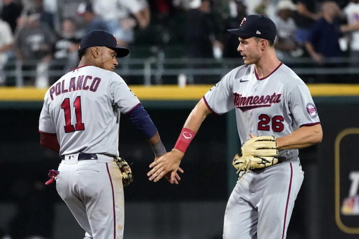 Minnesota Twins' Jorge Polanco (11) and Max Kepler celebrate the team's 7-2 win over the Chicago White Sox in a baseball game Wednesday, July 21, 2021, in Chicago. (AP Photo/Charles Rex Arbogast)