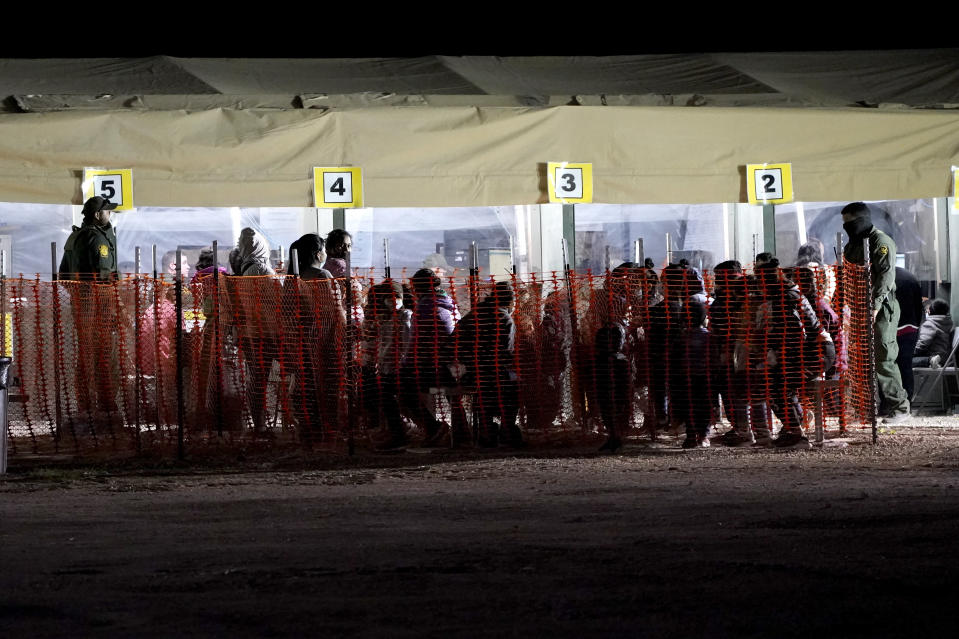 FILE - In this Friday, March 19, 2021, photo migrants are seen in custody at a U.S. Customs and Border Protection processing area under the Anzalduas International Bridge, in Mission, Texas. The Biden administration is facing growing questions about why it wasn't more prepared for an influx of migrants at the southern border. The administration is scrambling to build up capacity to care for 14,000 young undocumented migrants now in federal custody — and more likely on the way. (AP Photo/Julio Cortez, File)