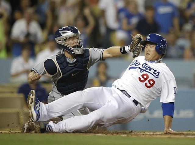 Los Angeles Dodgers starting pitcher Hyun-Jin Ryu, right, of South Korea, scores on a single by Yasiel Puig as San Diego Padres catcher Nick Hundley misses the throw during the second inning of a baseball game on Friday, Aug. 30, 2013, in Los Angeles. (AP Photo/Jae C. Hong)