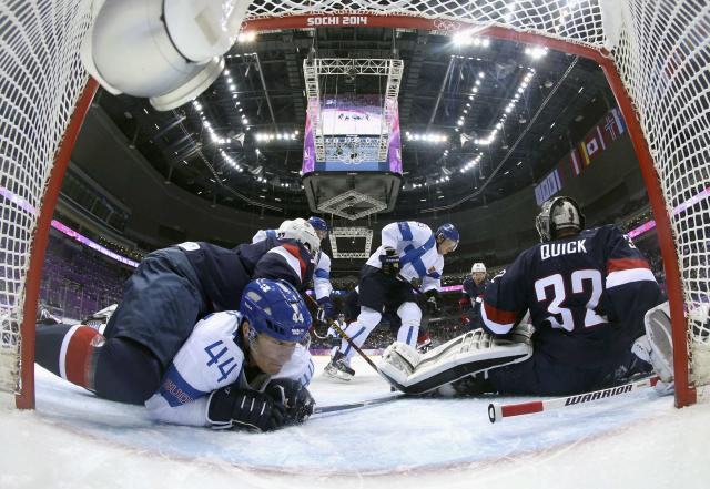 Team USA's goalie Jonathan Quick (R) makes a save against Finland's Jussi Jokinen (C) as Team USA's Ryan McDonagh lies on top of Finland's Kimmo Timonen (44) during the first period of their men's ice hockey bronze medal game at the Sochi 2014 Winter Olympic Games February 22, 2014. REUTERS/Martin Rose/Pool (RUSSIA - Tags: SPORT ICE HOCKEY OLYMPICS)