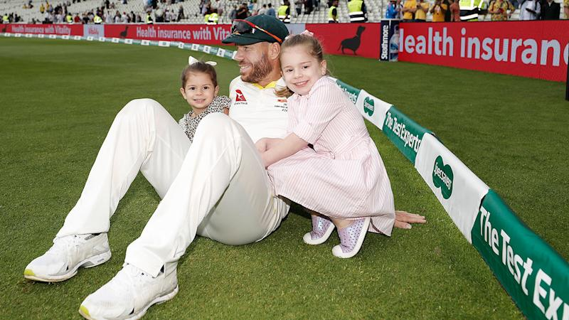 Pictured here, David Warner enjoys a moment after play with his two eldest daughters.