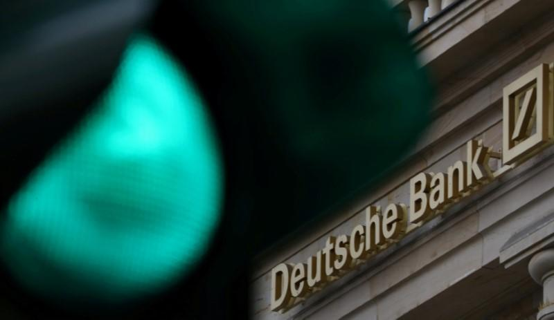 FILE PHOTO: A green traffic light is seen next to the logo of Germany's largest business bank, Deutsche Bank in Frankfurt
