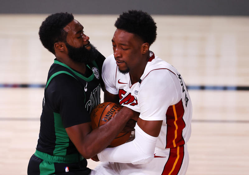 LAKE BUENA VISTA, FLORIDA - SEPTEMBER 25: Bam Adebayo #13 of the Miami Heat and Jaylen Brown #7 of the Boston Celtics fight for possession during the first quarter in Game Five of the Eastern Conference Finals during the 2020 NBA Playoffs at AdventHealth Arena at the ESPN Wide World Of Sports Complex on September 25, 2020 in Lake Buena Vista, Florida. NOTE TO USER: User expressly acknowledges and agrees that, by downloading and or using this photograph, User is consenting to the terms and conditions of the Getty Images License Agreement. (Photo by Mike Ehrmann/Getty Images)