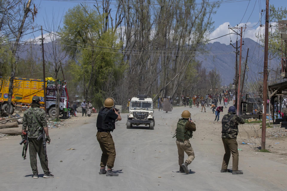 Indian policemen fire pellets at Kashmiri villagers during a protest near the site of a gunbattle in Pulwama, south of Srinagar, Indian controlled Kashmir, Friday, April 2, 2021. Anti-India protests and clashes have erupted between government forces and locals who thronged a village in disputed Kashmir following a gunbattle that killed three suspected militants. Police say the gunfight on Friday erupted shortly after scores of counterinsurgency police and soldiers launched an operation based on tip about presence of militants in a village in southern Pulwama district. (AP Photo/ Dar Yasin)