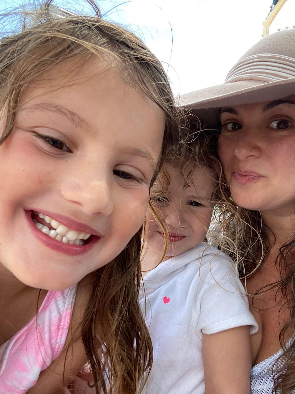 hilary young in a hat on the beach with her two daughters, 6 and 3.